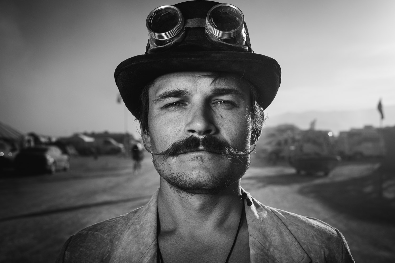 monochrome black and white Burning Man portrait of man with cylinder hat and mustache