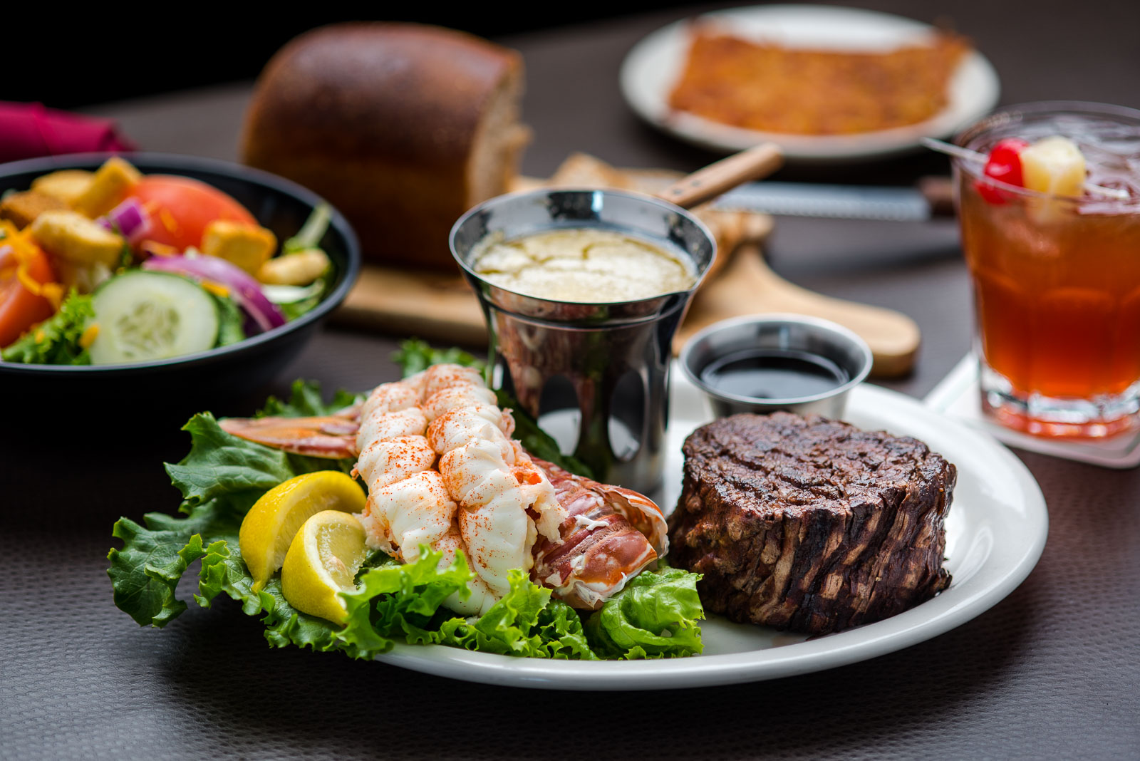 lobster, steak with an Old-Fashioned cocktail