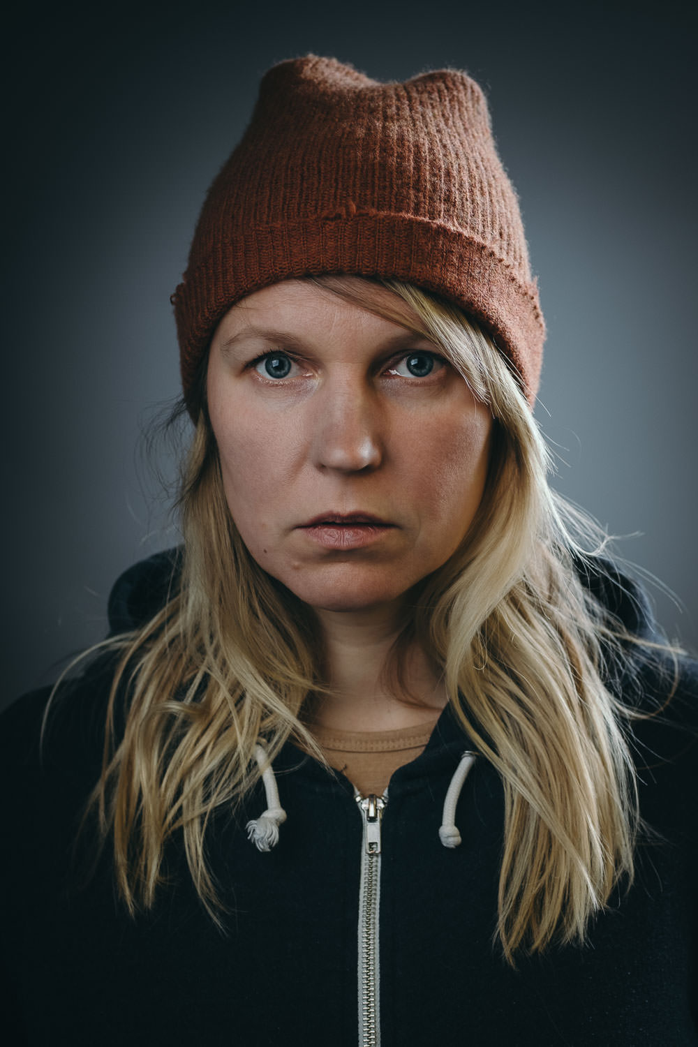 in studio headshot of a woman wearing a beanie for About Me page