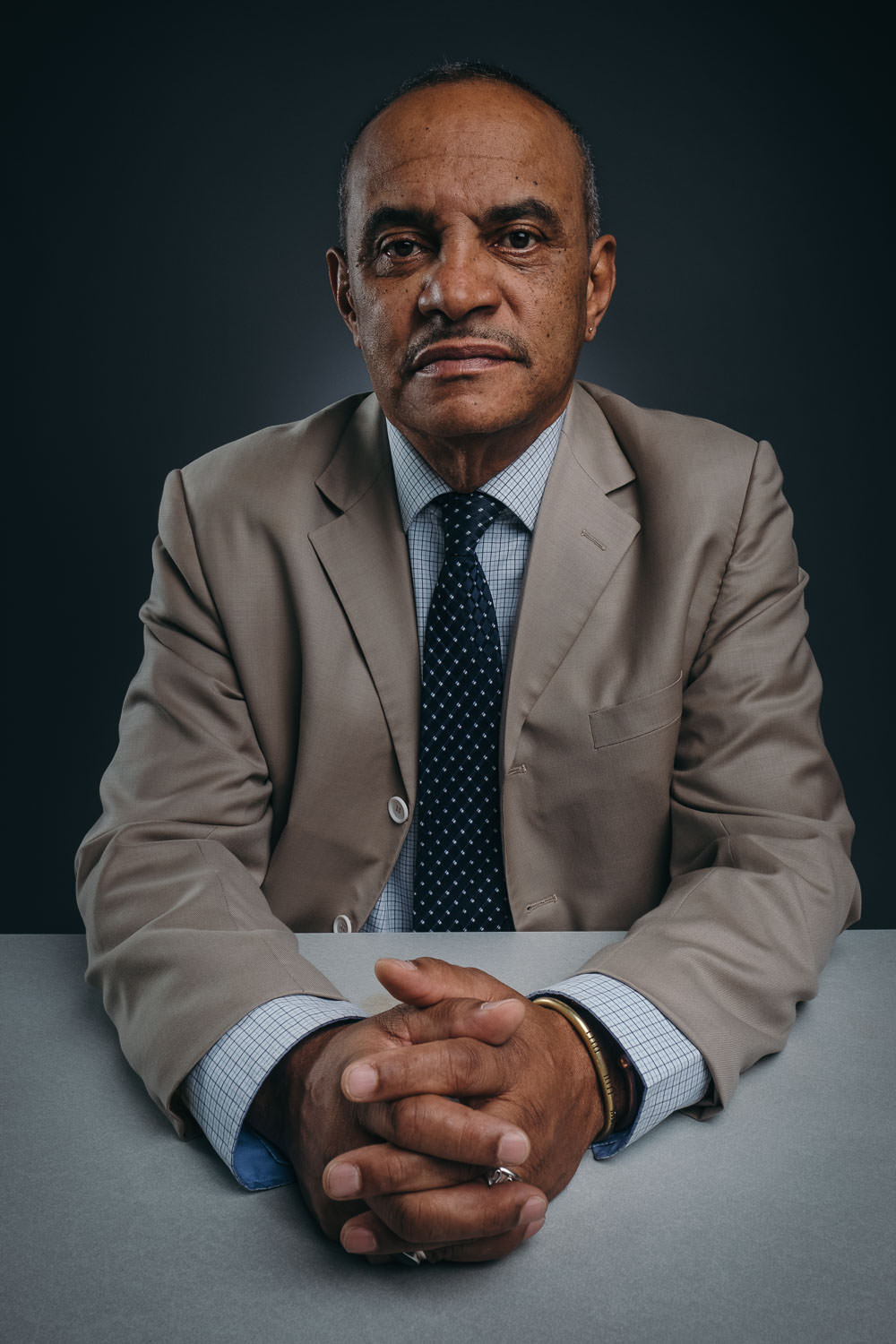serious portrait of African-American man sitting behind the table