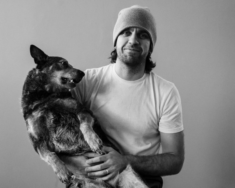 in studio portrait of Paulius Musteikis with his Australian Cattle dog