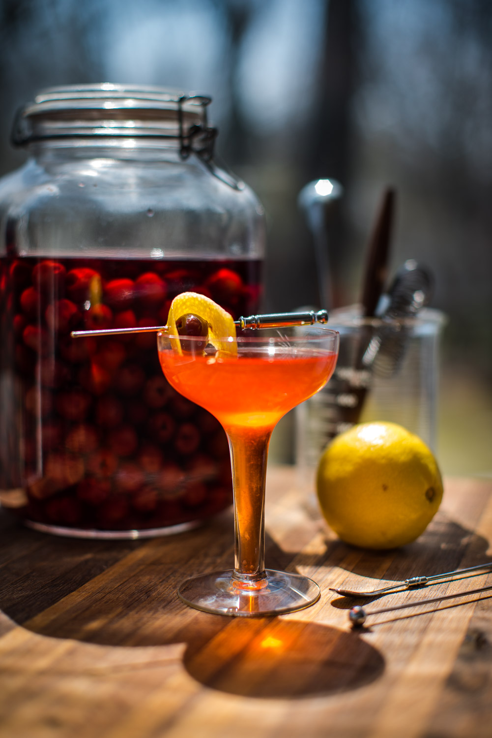 orange craft cocktail with a cherries and lemon