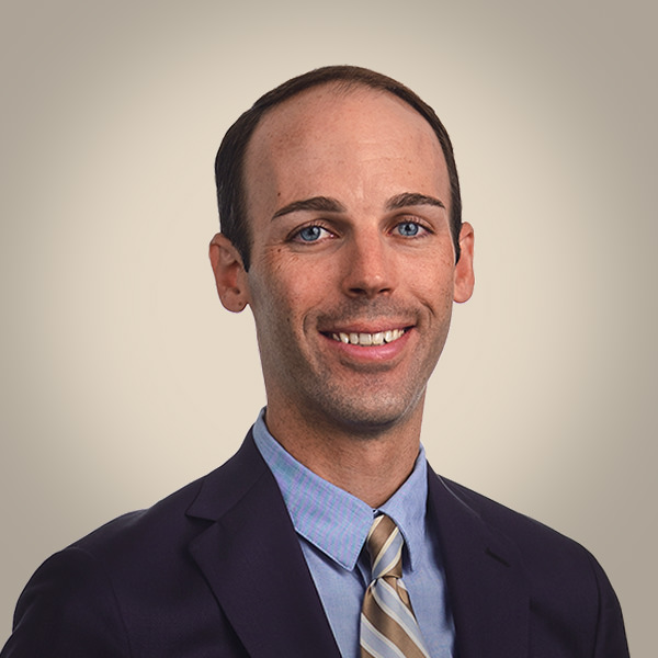 corporate headshot of smiling man in suit