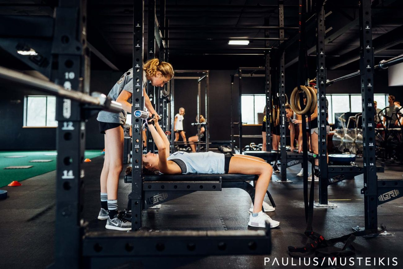 student is helping her female friend with weight lifting exercise at the gym